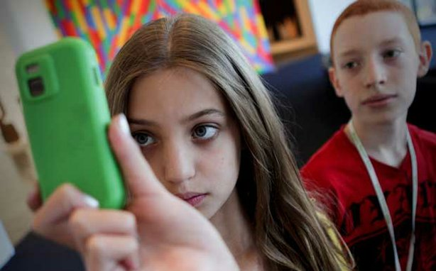 Promotional photo of a girl holding a cell phone at a camp for middle school ...