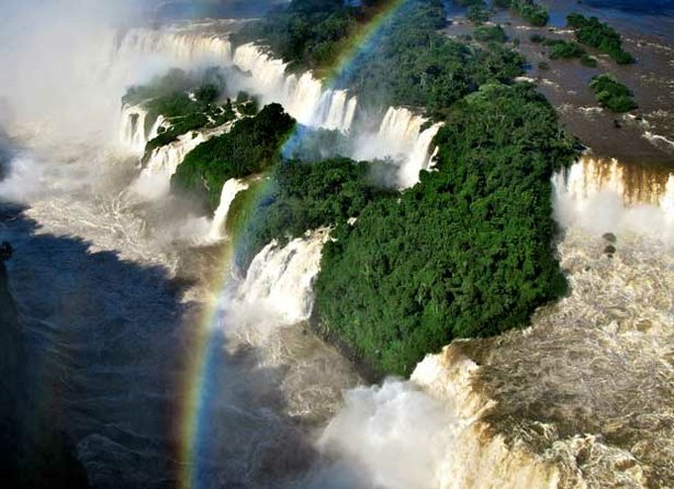 Spray high over Iguaçu Falls, on the border of Brazil and Paraguay, creates a...