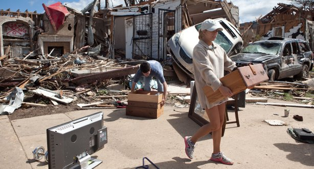 In the aftermath of a severe tornado, Kelly Giddens (R) helps University of A...