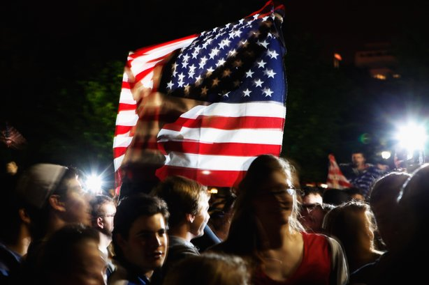 Students gather at the fence on the north side of the White House, pose for photographs, chant 'U.S.A.! U.S.A.!' and sing the Star Spangled Banner while U.S. President Barack Obama announces the death of Osama Bin Laden during a late evening statement to the press in the East Room of the White House May 1, 2011 in Washington, DC.