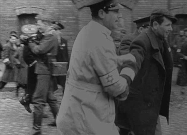 A still showing Nazi filmmakers and Jews on the streets of the Warsaw Ghetto,...