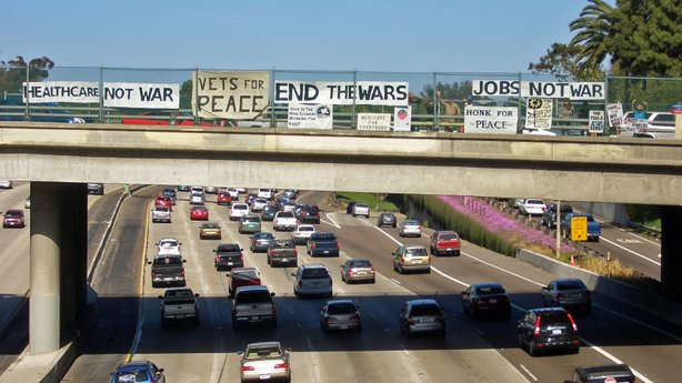 San Diego Veterans for Peace hold a banner demonstration on a freeway overpass.