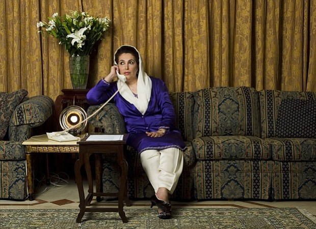 Benazir Bhutto sits on a couch talking on the phone.