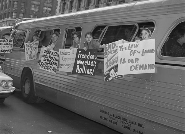 Freedom Riders hang posters from a bus. From May until November 1961, more than 400 black and white Americans risked their lives — and many endured savage beatings and imprisonment — for simply traveling together on buses and trains as they journeyed through the Deep South.