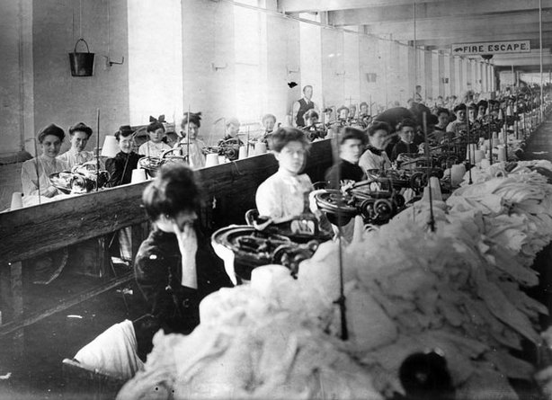 "Women sitting at sewing machines in the Triangle Shirtwaist Factory, with piles of white fabric in front of them. A sign attached to the ceiling at the back says ""Fire Escape"" and has a hand pointing to a window."