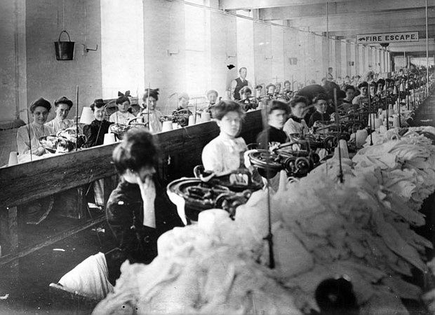 Women sitting at sewing machines in the Triangle Shirtwaist Factory, with pil...