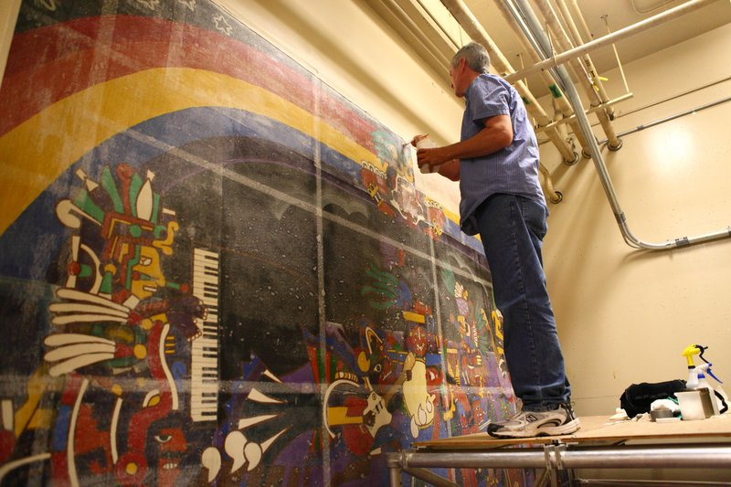 Conservator Gary Hulbert layers the mural with resin, tissue paper and fabric...