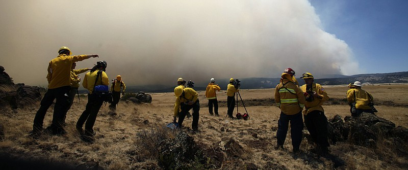 Members of the media set up in front of smoke from the Wallow fire June 8, 20...