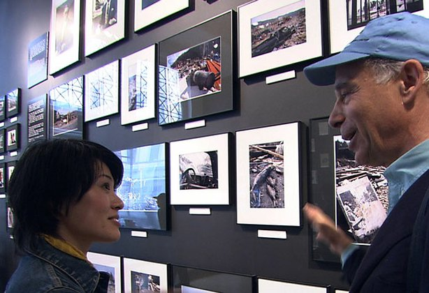 Promotional photo of Japanese photographer Mayumi Suzuki talking in front of a wall of photos.