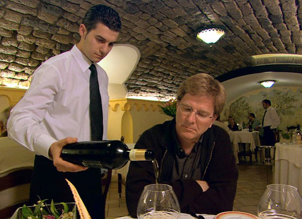 Rick Steves enjoys some wine with dinner while in Italy.