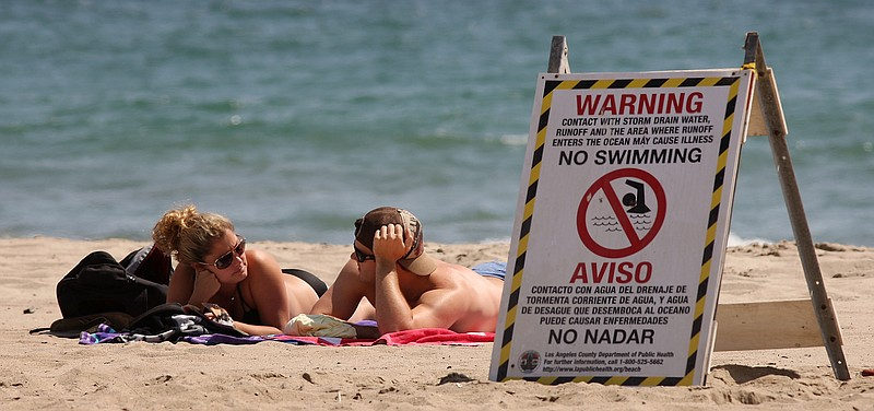 A sign warns beach-goers to stay out of the water because of contamination.