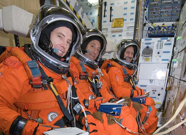 Seated on the mid-deck are astronauts Andrew J. Feustel (foreground), Michael...