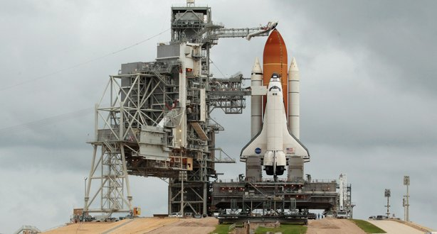 Hundreds of people gather near launch pad 39A to photograph and be photographed with the space shuttle Atlantis one day before its scheduled launch at Kennedy Space Center July 7, 2011 in Cape Canaveral, Florida.