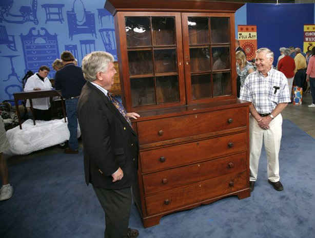 "At ""Antiques Roadshow"" in San Antonio, Texas, this man brings in a gigantic Texas desk and bookcase, circa 1850. After a careful examination, appraiser Dean Failey of Christie's connects this piece to the growing population of German cabinetmakers in Texas during the 1840s. The proud owner stands tall next to this formidable piece of furniture, as Failey estimates its value at $7,000 to $10,000."