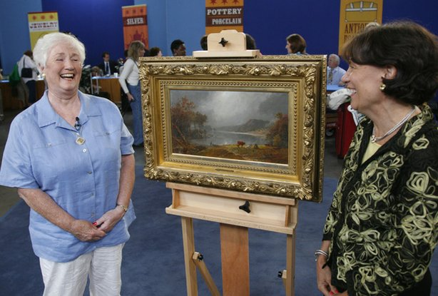 "A guest (left) at ""Antiques Roadshow"" in Grand Rapids is thrilled to discover..."