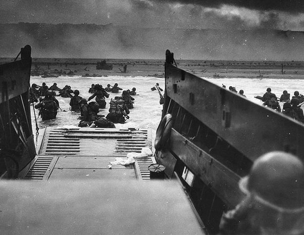"Normandy Invasion, June 1944. Army troops wade ashore on ""Omaha"" Beach during the D-Day landings, June 6, 1944. They were brought to the beach by a Coast Guard manned LCVP."