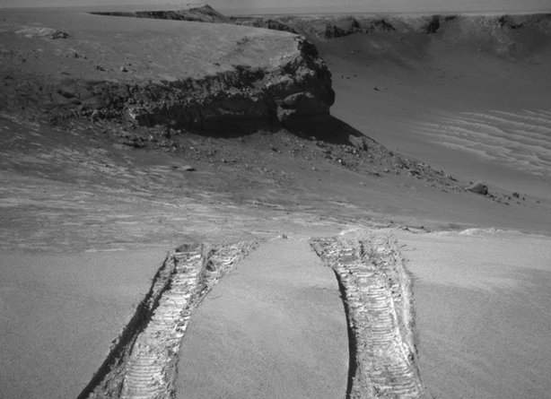 "NASA's Mars Exploration Rover Opportunity climbed out of ""Victoria Crater"" following the tracks it had made when it descended into the 800-meter-diameter bowl nearly a year earlier."