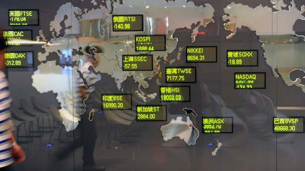 A man walked past a billboard showing global stock indices at the Taiwan Stoc...