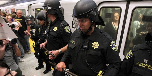 Bay Area Rapid Transit (BART) police keep back demonstrators that are trying ...