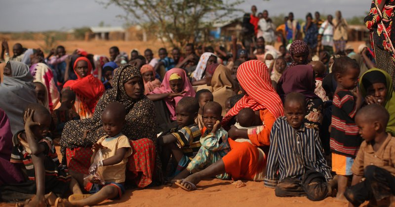 Somalian refugees wait in the registration area of the Ifo refugee camp which...