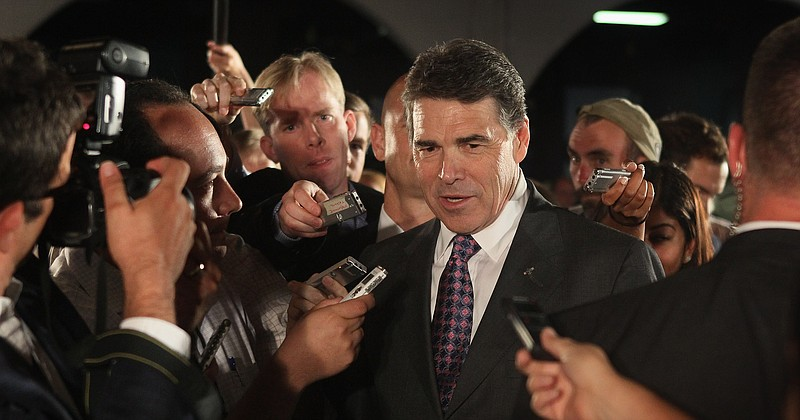 Republican presidential candidate Texas Governor Rick Perry (C) arrives at th...