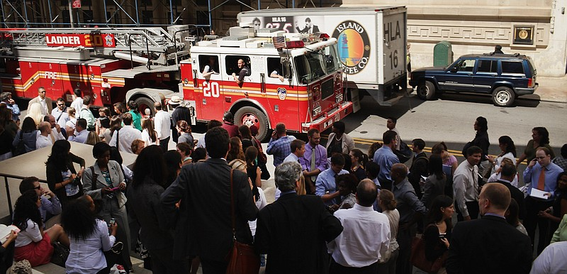 People stand outside of their buildings after being evacuated following an ea...