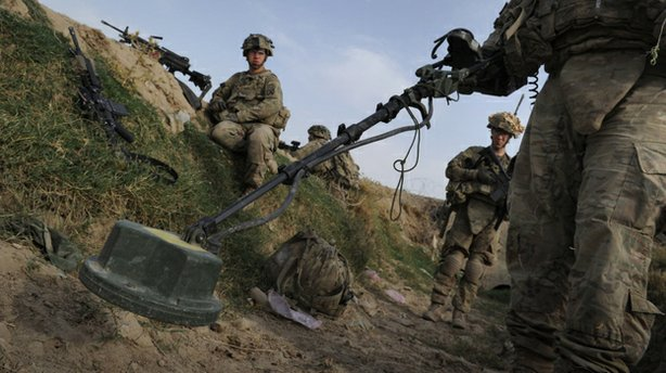U.S. soldiers check for land mines on a canal running through Highway 1 in Af...