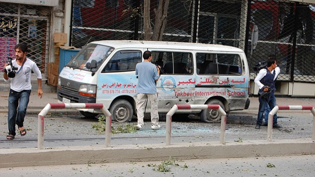 Journalists stand near a bullet-ridden van during Tuesday's attack in Kabul.