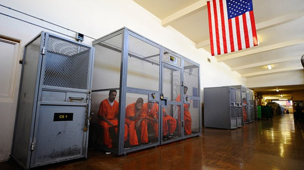 Inmates at California's Chino State Prison sit inside a metal cage in the hal...