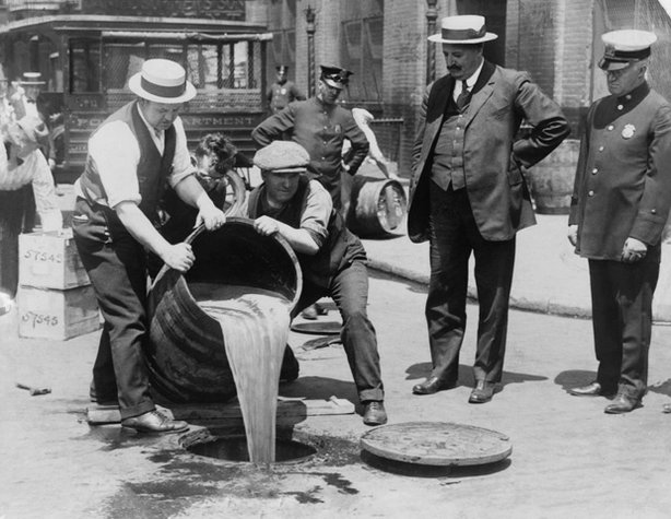 New York City Deputy Police Commissioner John A. Leach, right, watching agents pour liquor into sewer following a raid, ca. 1921. After the Mullan-Gage Act was repealed in 1923, New York police were no longer bound to enforce Prohibition.