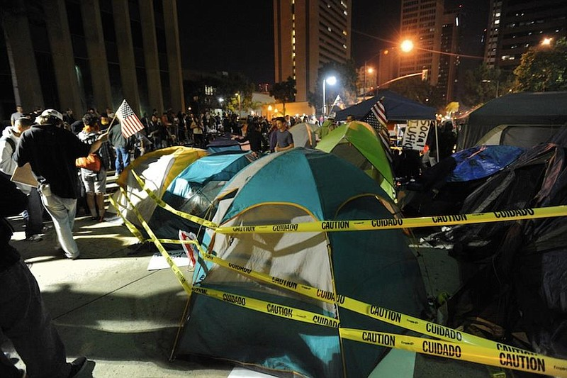 Yellow police tape surrounds tents at Occupy San Diego as protesters rally, o...