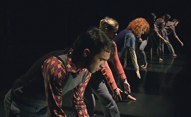 "A performance photo of dancers. Troika Ranch, an award-winning international dance company struggles to create a new, experimental dance work exploring the repetitions of the modern world in which ordinary people find themselves trapped in ""Loopdiver: The Journey Of A Dance."""