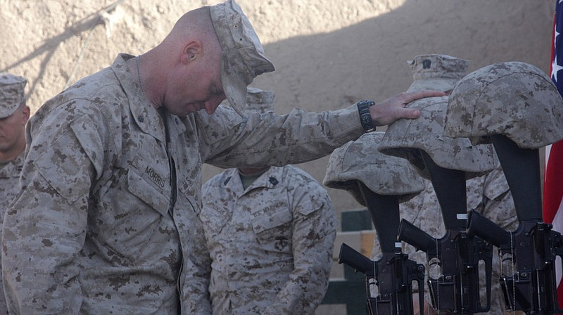Lt. Col. Jason Morris pays his respects at a memorial service in Sangin, Afgh...