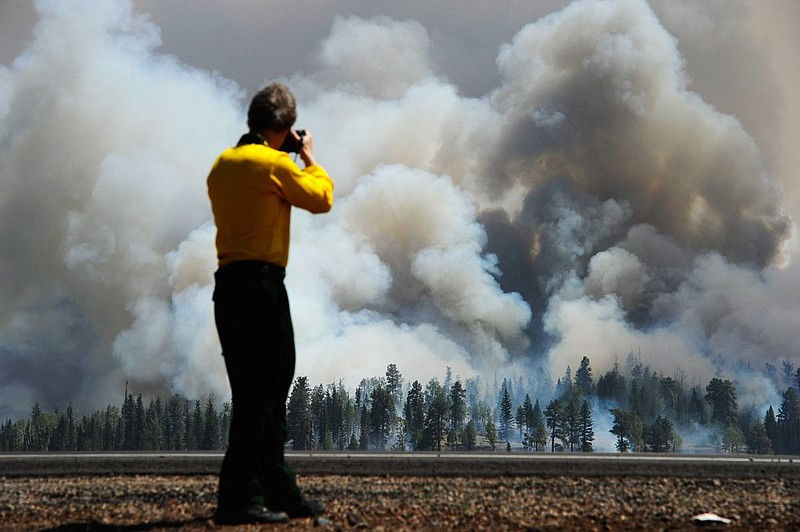 A photographer looks on as smoke rises around the Lee Valley Recreational are...