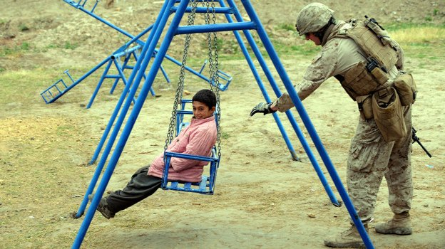 A U.S. Marine pushes a child on a swing in southern Afghanistan on March 4. A...