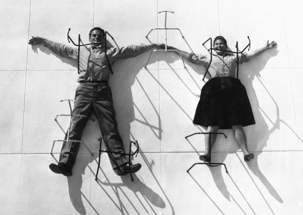 """Charles and Ray Eames """"pinned"""" by chair bases, 1947."""