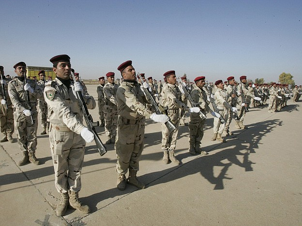 Iraqi soldiers take part in a graduation parade in Kirkuk on Monday. The oil-...