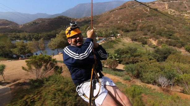 Host Jorge Meraz flies high across zip-lines on the canopy tour at the Las Cañadas Campground.