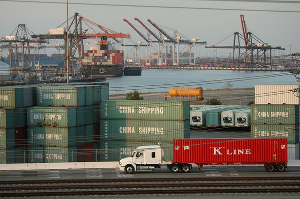 A truck passes shipping containers at China Shipping at the Ports of Long Bea...