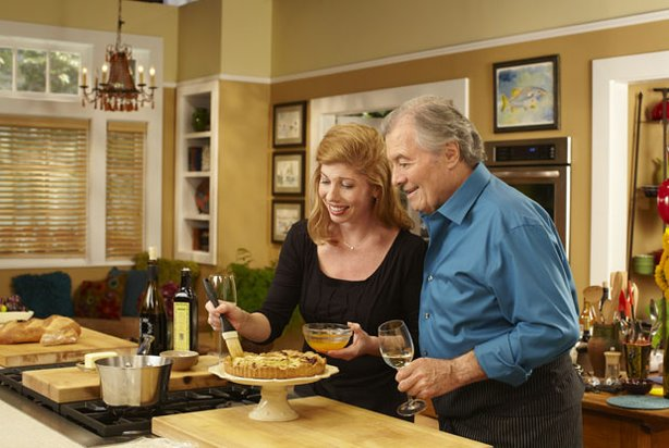 Jacques Pépin enjoys a glass of wine while his daughter, Claudine glazes a tart.