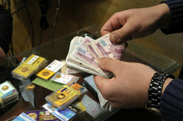 An Iranian man counts banknotes after exchanging a gold coin for cash in Tehr...