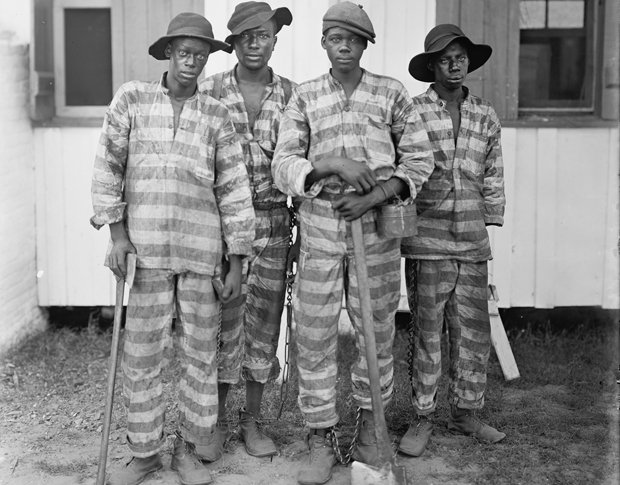 Historical photo of four convict laborers in shackles.