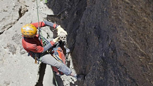 Climber Pete Athans removes a skull from an eroded cliffside cave in Nepal's Mustang region.