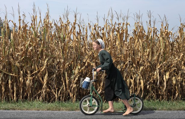 An Amish girl rides her foot push bike down the road.