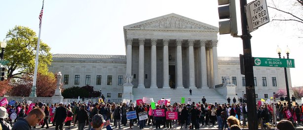 People participate in a protest on the second day of oral arguments for the Patient Protection and Affordable Care Act in front of the U.S. Supreme Court building on March 27, 2012 in Washington, DC.