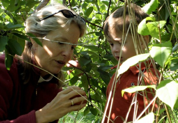 "A woman and child take a closer look at a piece of fruit from a tree in the film ""Mother Nature's Child: Growing Outdoors In The Media Age."""