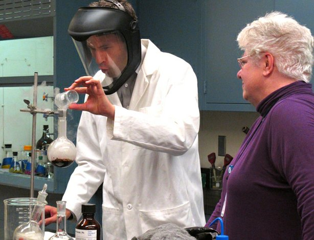 In a chemistry lab at New Mexico Tech, Senior Research Scientist Christa Hockensmith (right) shows David Pogue (left) how to test for elements in bomb debris.