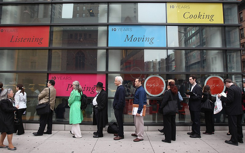 People stand in a line that stretched around the block to enter a job fair he...