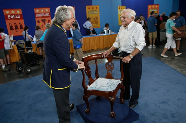 At ANTIQUES ROADSHOW in Atlanta, Ga., appraiser Michael Flanigan (left) tells the delighted owner of this circa 1760 New York Chippendale corner chair—purchased as part of a collection for $750-$800—that the piece actually is valued between $250,000-$300,000.