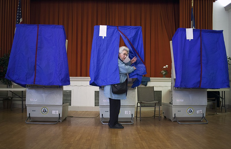 Lilyan Maitan stands in a voting booth during the Republican primary election...